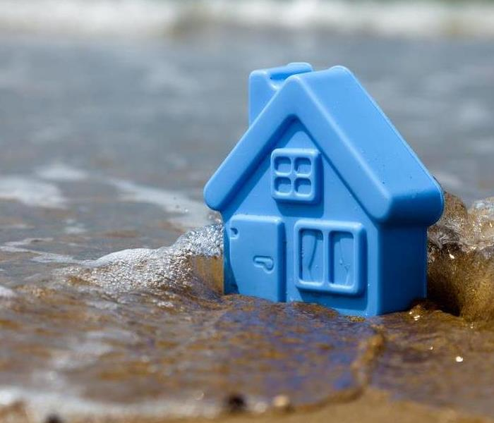 Little blue toy house being washed away by water